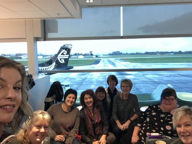 Women smiling in front of an Air New Zealand aeroplane at the airport.