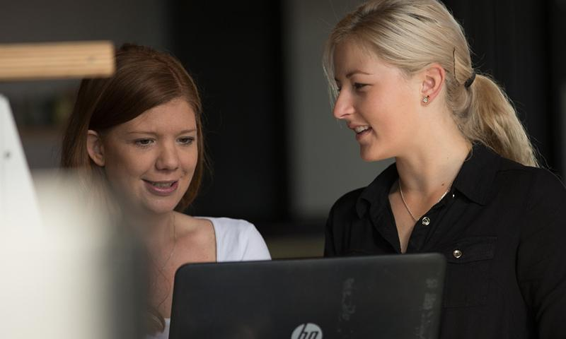 Two women stand at a screen. The boss shows her employee how to access her pay-to-date information online, as single touch payroll will bring an end to group certificates.