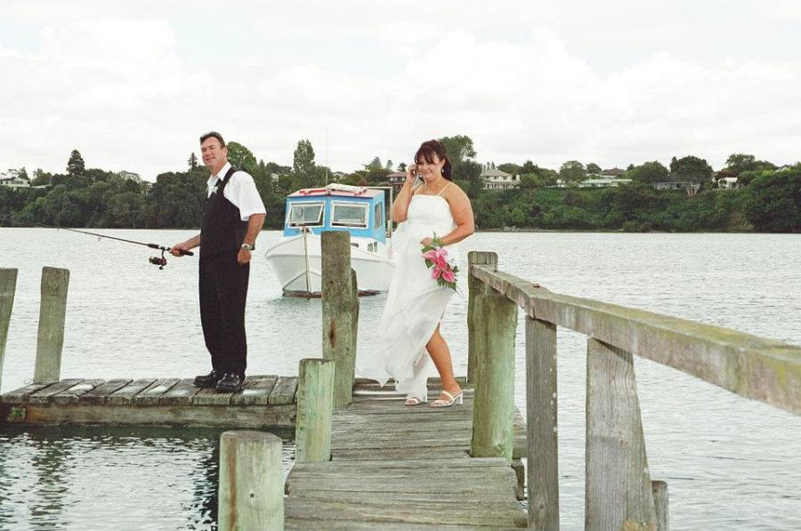 Janine and her husband on a pier on their wedding day