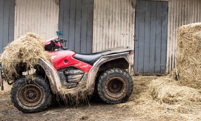 A muddy red four-wheel motorbike showing signs of wear and tear, and depreciation.