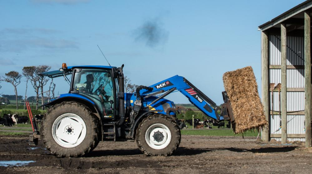 Simon uses his tractor to move hay bales into his shed