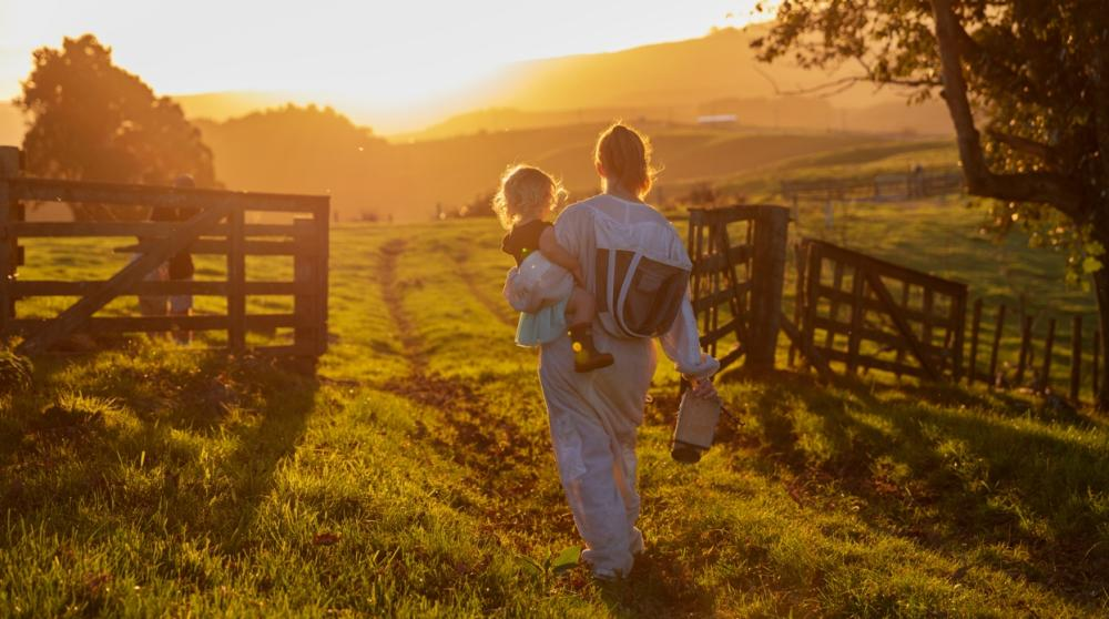 Hannah walks out of the farm gate towards the sunset with Alice on her hip.