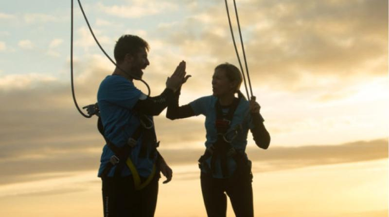 Two people on top of the Sky Tower high-fiving