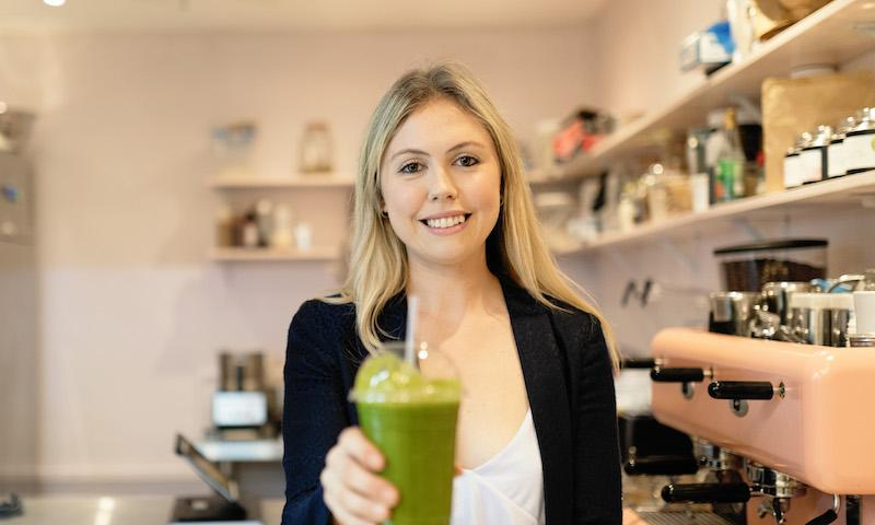Olivia Scott, owner of The Raw Kitchen, holding a green smoothie