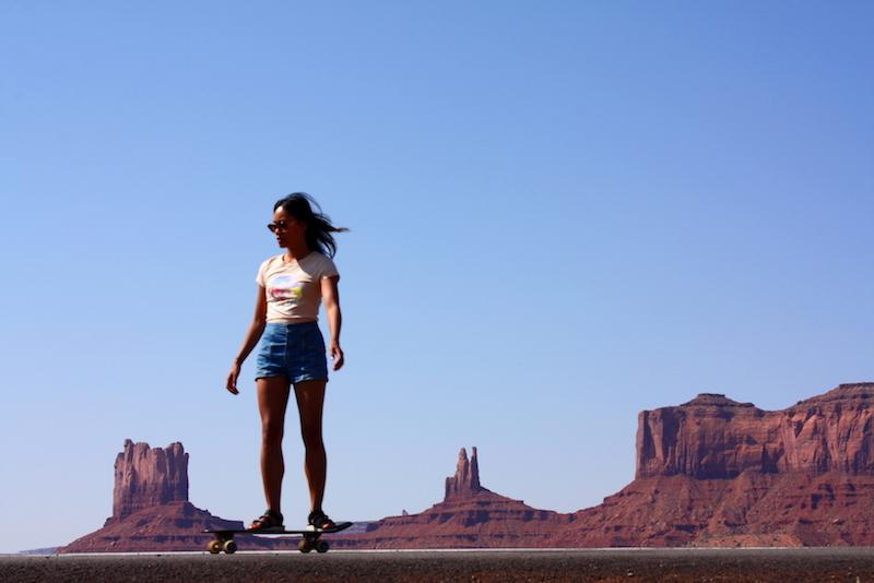Claire skateboarding down the road at Monument Valley in Utah