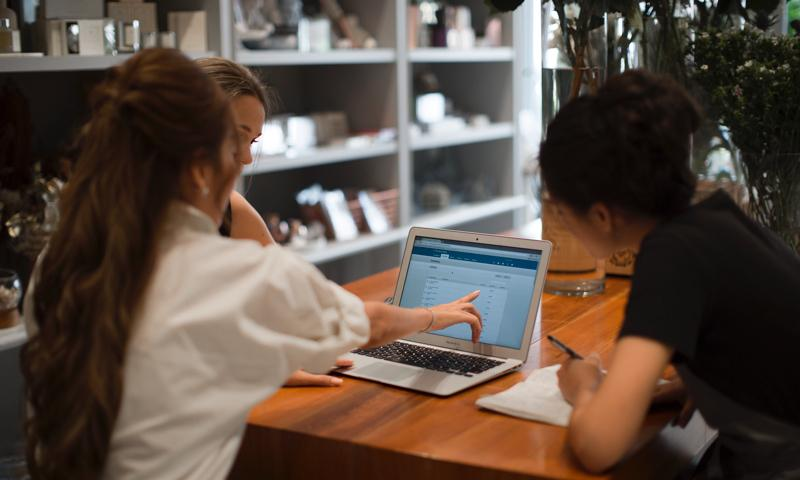 Three people sit at a laptop inspecting a set of small business accounts - in this case created using accrual based accounting.